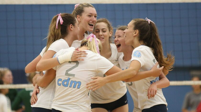 Corona del Mar celebrates a big point against Edison during Surf League girls volleyball on Tuesday.