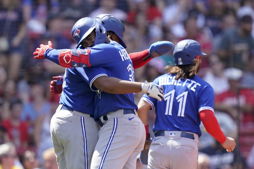 Toronto Blue Jays right fielder Teoscar Hernandez, front left, celebrates with Vladimir Guerrero Jr., behind left, and Bo Bichette (11) after Hernandez hit a three-run home run in the fourth inning of a baseball game against the Boston Red Sox, Sunday, June 13, 2021, in Boston. The Blue Jays won 18-4. (AP Photo/Steven Senne)