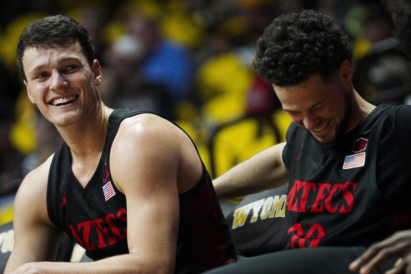 San Diego State forward Yanni Wetzell (left) and guard Jordan Schakel laugh on the bench after a teammate accidentally stepped out of bounds while not under pressure during game against Wyoming on Wednesday in Laramie, Wyo.