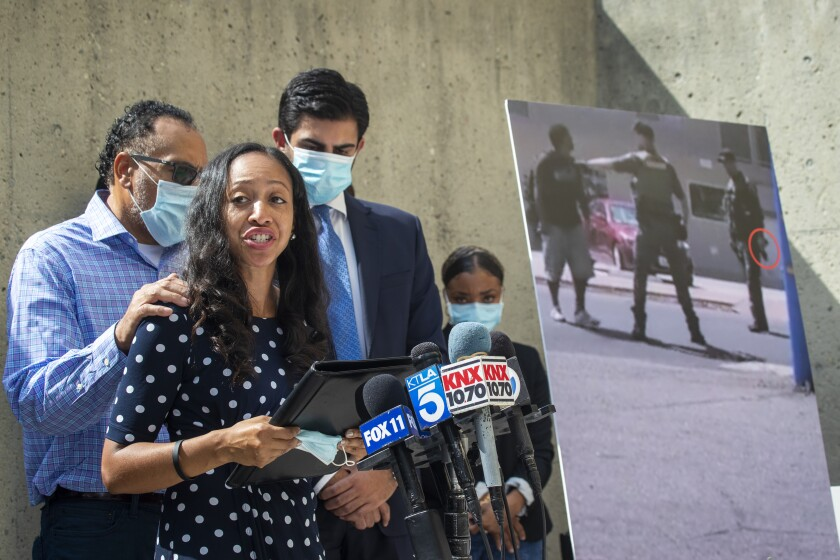 Latoya Reinhold, widow of Kurt Reinhold, reads a prepared statement at a news conference in Santa Ana.