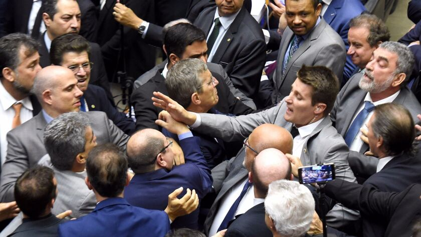 Brazilian lawmakers fight during a session at the Chamber of Deputies in Brasilia on Wednesday as they debated whether President Michel Temer should face trial for alleged corruption.