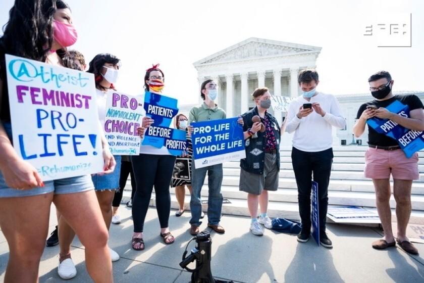 Manifestantes antiaborto escuchan mientras otros leen un fallo del Tribunal Supremo
