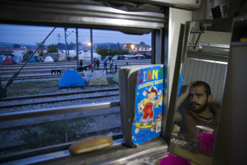 In this Sunday, May 8, 2016 photo, 23-year old Mohamed from Syria looks out of the window from the cabin of a train that he lives  in, in the sprawling refugee and migrant tent city in Idomeni, on Greece's northern border with Macedonia. (AP Photo/Petros Giannakouris)