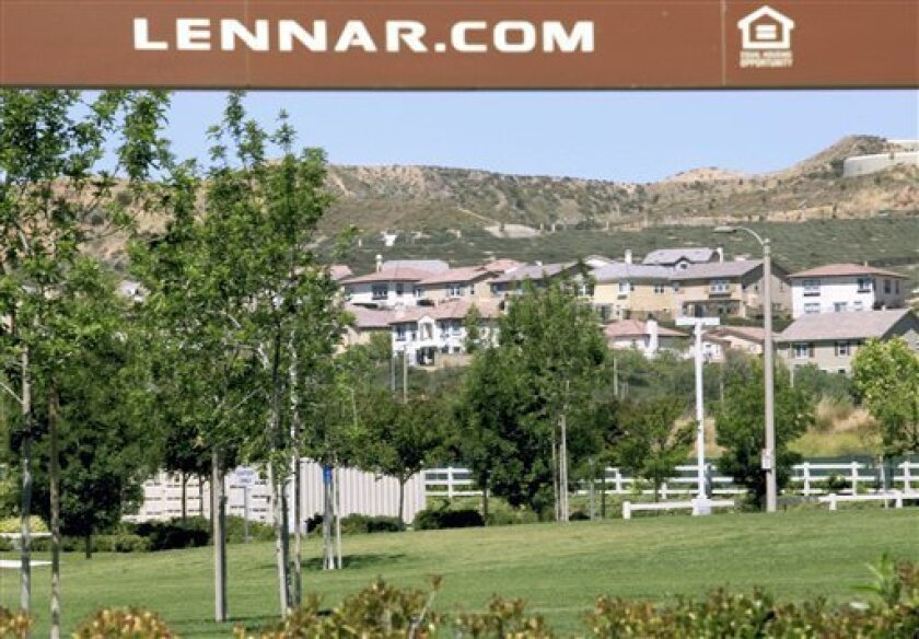 In this photo taken June 22, 2011, new homes are seen under a Lennar banner in Santa Clarita, Calif. Lennar Corp.'s net income dropped 65 percent in its fiscal second quarter Thursday, June 23, 2011, partly on the absence of an income tax benefit but managed to beat analysts' expectations as home deliveries declined.(AP Photo/Damian Dovarganes)