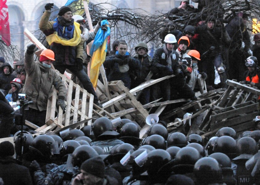 Protesters defend their barricades in front of anti-riot police on Independence Square in Kiev early Wednesday.
