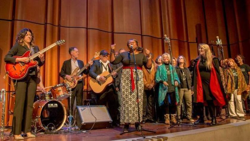 The Choir onstage, with co-founders Steph Johnson (left, with guitar) and Nina Deering (right, with red scarf)