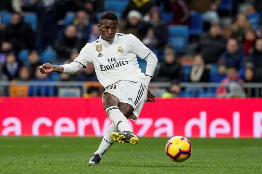 El delantero brasileño del Real Madrid, Vinicius Jr., golpea el balón para conseguir el segundo gol del equipo madridista durante el encuentro correspondiente a la jornada 22 de primera división que disputaron frente al Alavés en el estadio Santiago Bernabéu, en Madrid. EFE