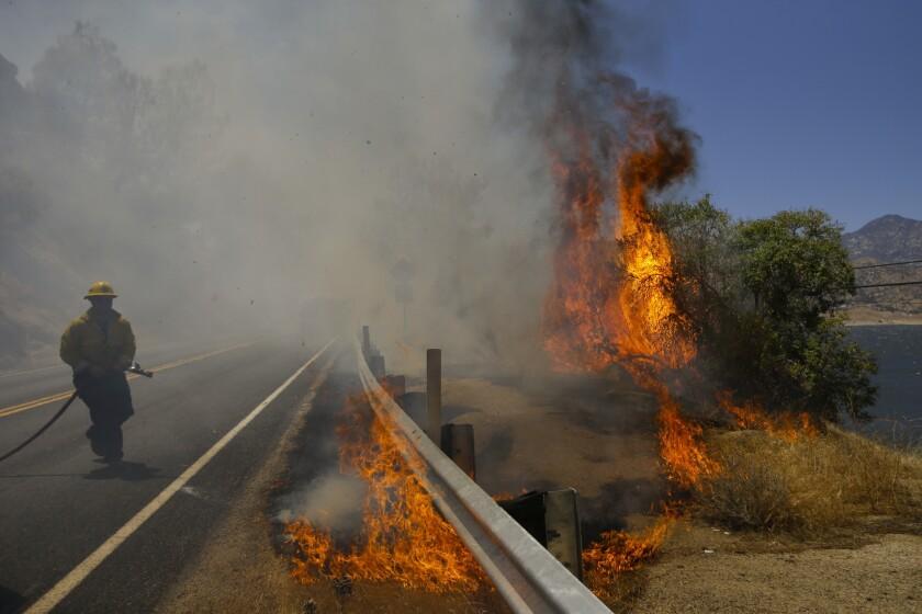 Un bombero trata de apagar un incendio al lado de la Highway 178, el viernes 24 de junio del 2016 en Lake Isabella, California. Un voraz y mortal incendio que arde en el centro de California ha quemado 200 casas y otras instalaciones, aunque bomberos dijeron el domingo 26 de junio del 2016 que un leve viento estaba ayudando a contener el siniestro. (Foto AP /Jae C. Hong)