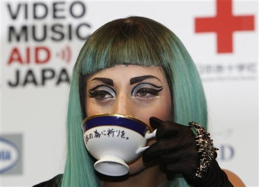 "Lady Gaga poses for photographers with a coffee cup with a message in Japanese ""Pray for Japan"" during a press conference to promote of MTV Video Music Aid Japan in Tokyo, Thursday, June 23, 2011. Lady Gaga said that she will sell the coffee cup at auction and donate the money for the tsunami-hit northeastern Japan. (AP Photo/Shizuo Kambayashi)"