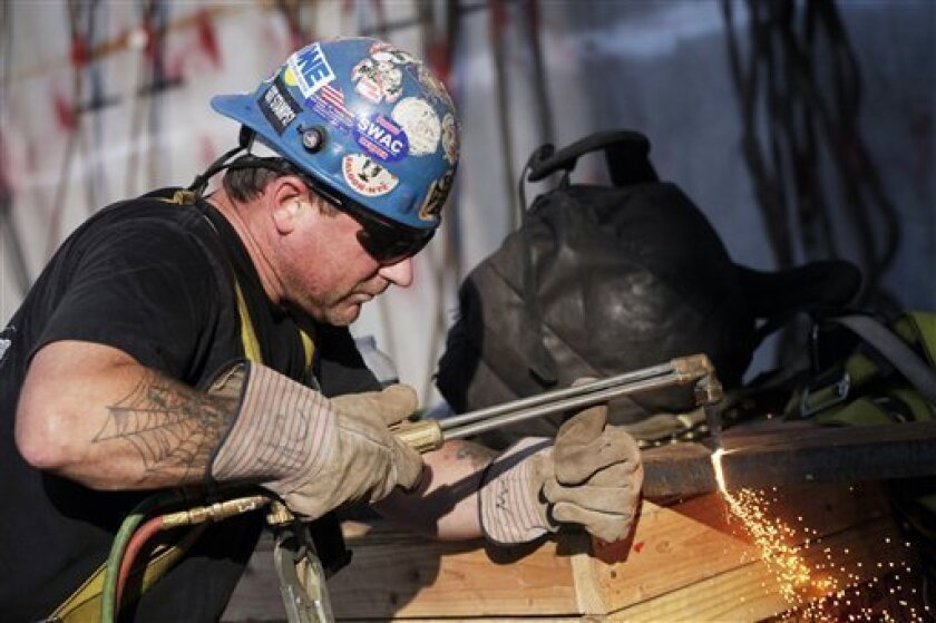 In this Aug. 2, 2012 photo, ironworker Stephen MacGray cuts a steel brace at the World Trade Center construction site, in New York. U.S. employers added 163,000 jobs in July, a hopeful sign after three months of sluggish hiring. The Labor Department said Friday, Aug. 3, 2012, that the unemployment