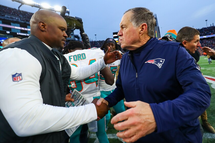 Miami Dolphins coach Brian Flores shakes hands with New England Patriots coach Bill Belichick.