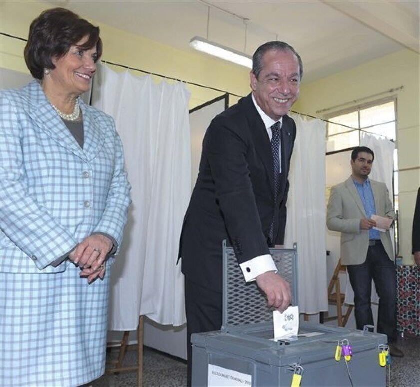 Maltese Prime Minister Lawrence Gonzi smiles for media as he casts his ballot and his wife Catherine Callus looks on, in Valletta, Malta, Saturday, March 9, 2013. Maltese head to the polls Saturday to decide whether to grant the center-right Nationalist Party a fourth straight term or give the oppo
