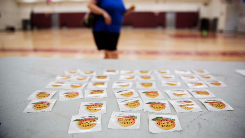 """Stickers reading """"I'm a Georgia Voter"""" sit on a table as a voter leaves a polling site Tuesday, July 26, 2016, in Atlanta."""