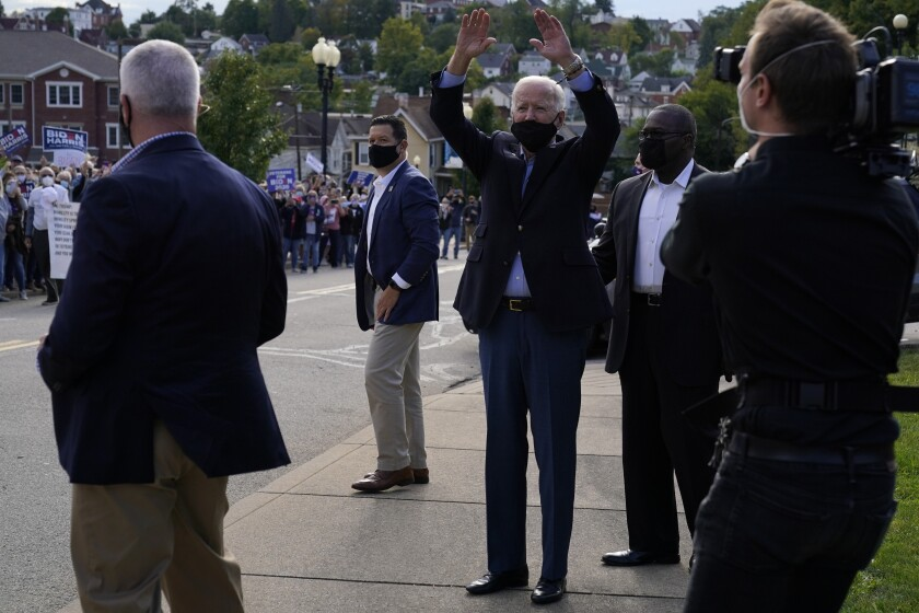 Joe Biden, wearing a mask, raises both arms to wave to supporters