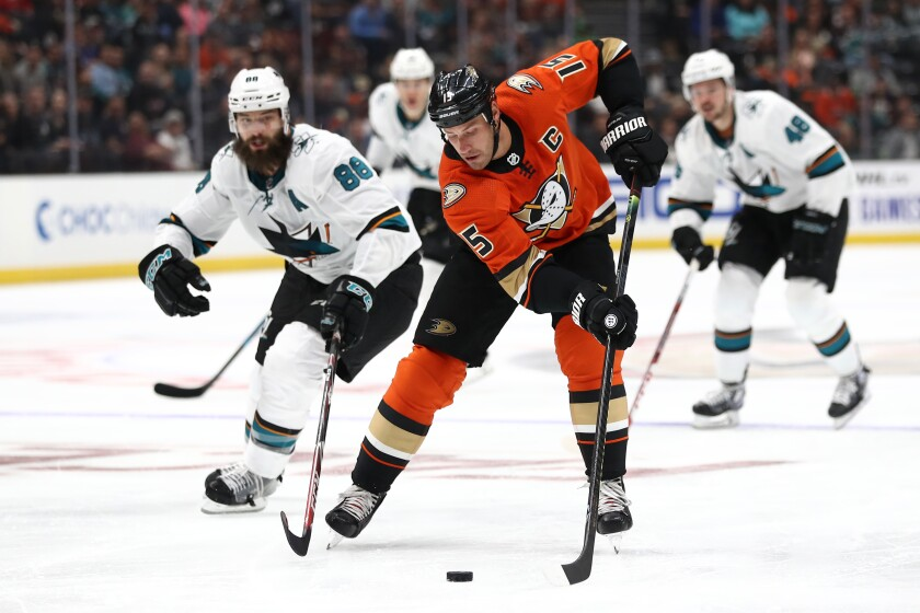 The Ducks' Ryan Getzlaf controls the puck past the Sharks' Brent Burns at Honda Center on Saturday night.