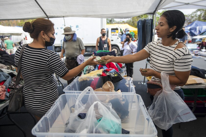 One woman buys clothing from another at the Los Angeles City College swap meet.