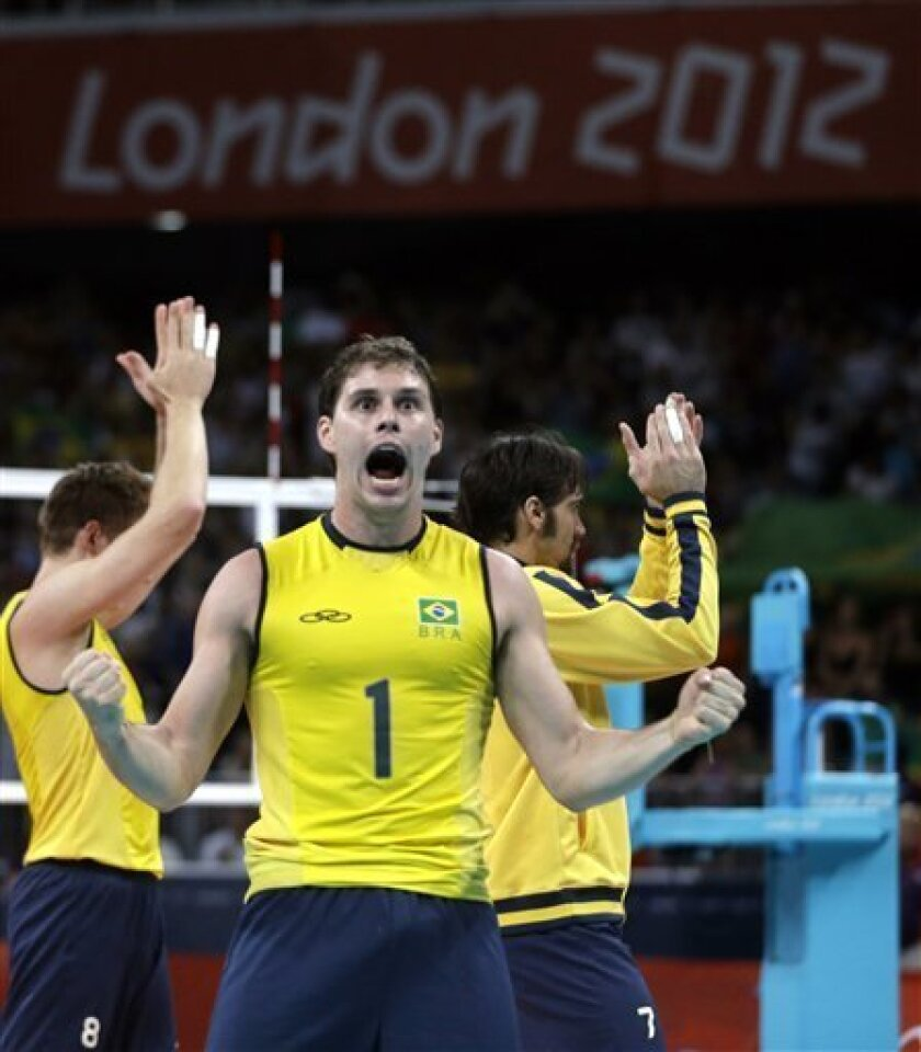 Brazil's Bruno Rezende celebrates his team's victory over Italy in a men's semifinal volleyball match at the 2012 Summer Olympics, Friday, Aug. 10, 2012, in London. (AP Photo/Jeff Roberson)