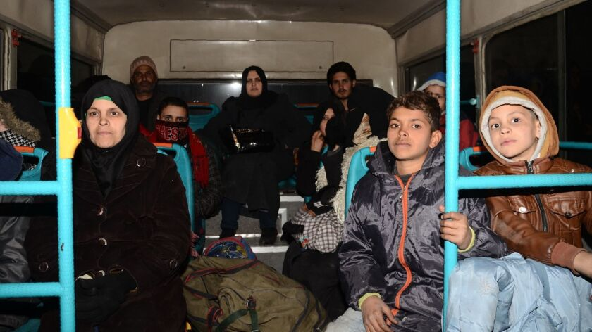 Syrian families from various eastern districts of Aleppo are evacuated by bus on Nov. 27, 2016, as Syrian government forces continue their advance toward rebel-controlled districts.