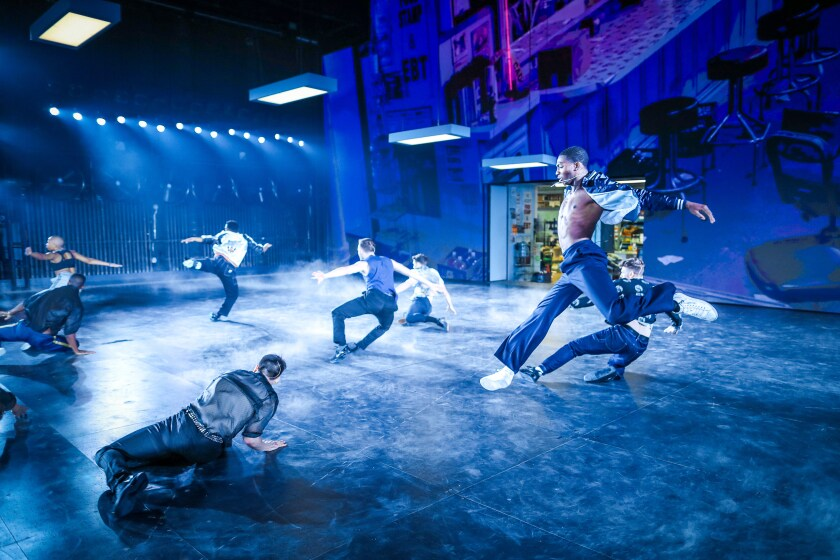 "Dharon E. Jones as Rif, leader of the Jets, amid the scenic and lighting design of Jan Versweyveld in the ""West Side Story."""