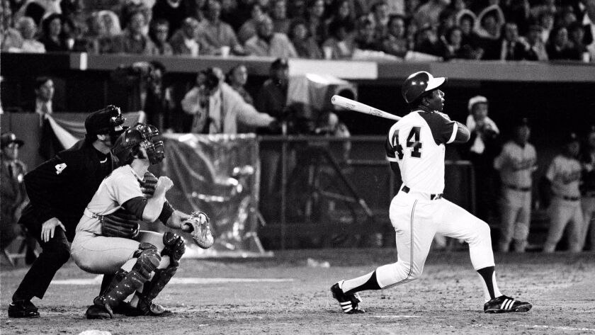 Hank Aaron watches career home run No. 715 sail over the left-field fence in an Atlanta Braves home game in 1974.
