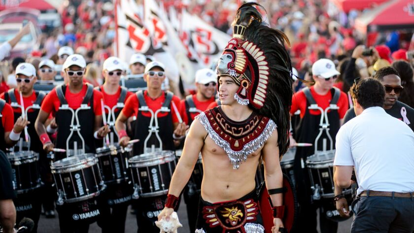 San Diego State's Aztec Warrior leads the band and football team during the Warrior Walk through the alumni section of the SDCCU Stadium parking lot before a football game last fall.