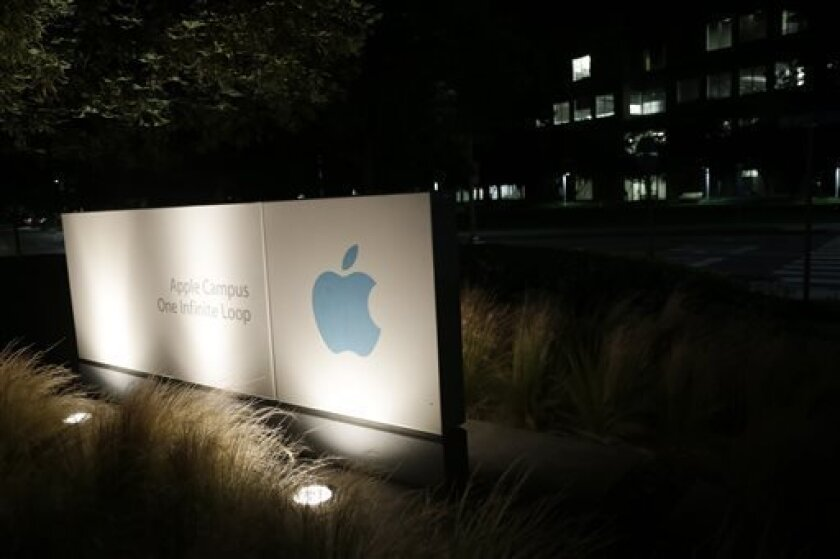 """FILE - In a Friday, June 7, 2013 file photo, a sign displays the Apple logo outside of the company's headquarters in Cupertino, Calif. A federal judge ruled Wednesday, July 10, 2013 that Apple Inc. broke antitrust laws and conspired with publishers to raise electronic book prices, citing """"compelling evidence"""" from the words of the late Steve Jobs. U.S. District Judge Denise Cote said Apple knew that no publisher could risk acting alone to try to eliminate Amazon.com's $9.99 price for the most po"""