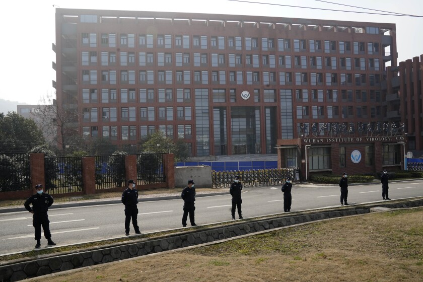 People in black uniforms stand in a line along a roadway outside a multistory building.