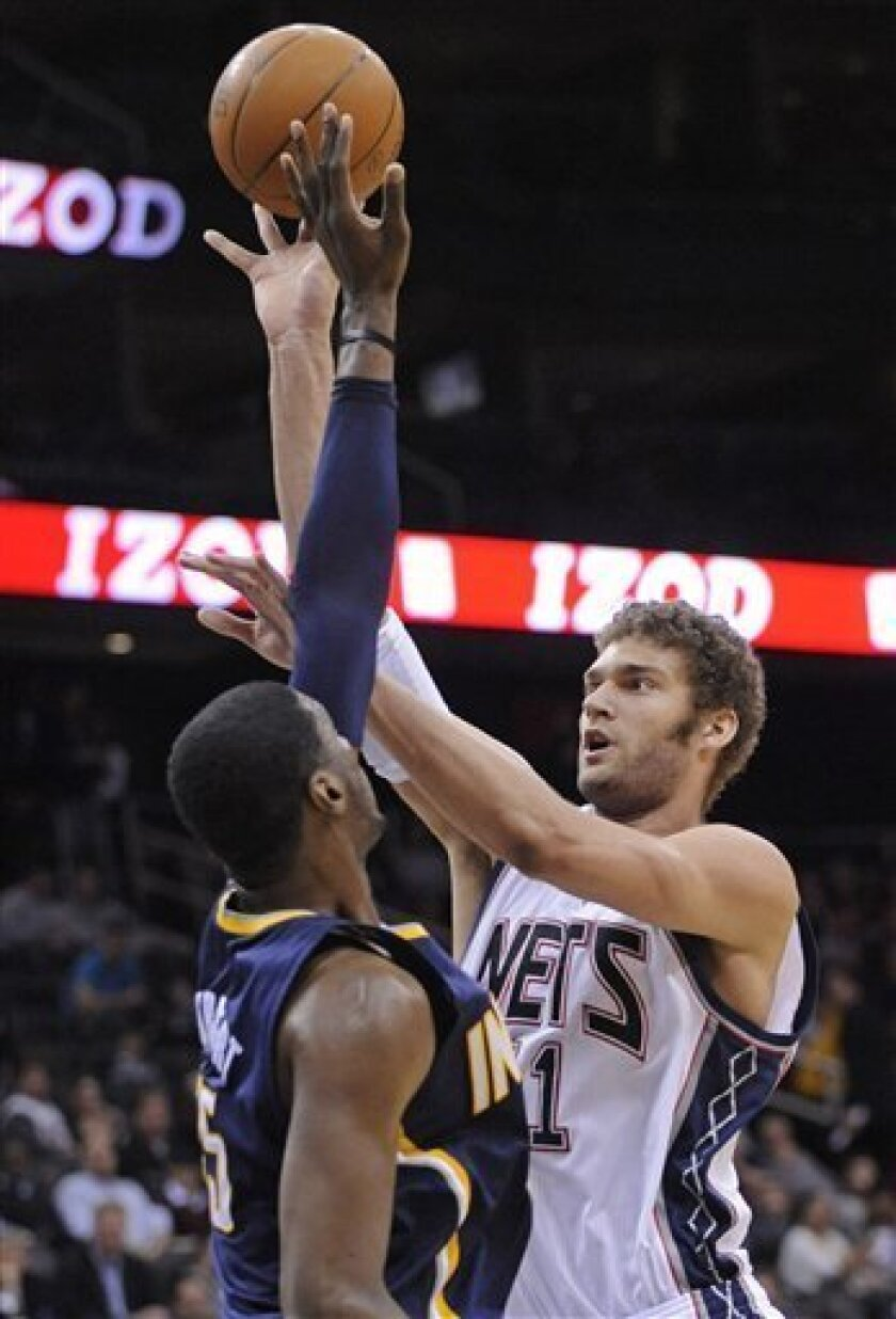 New Jersey Nets' Brook Lopez, right, puts up a shot over Indiana Pacers' Roy Hibbert during the second quarter of an NBA basketball game Monday, March 21, 2011, in Newark, N.J. (AP Photo/Bill Kostroun)