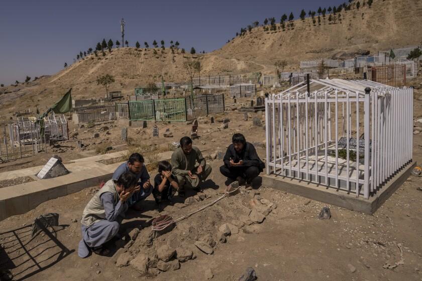 la familia Ahmadi reza junto a las tumbas de sus 10 familiares, incluidos siete niños