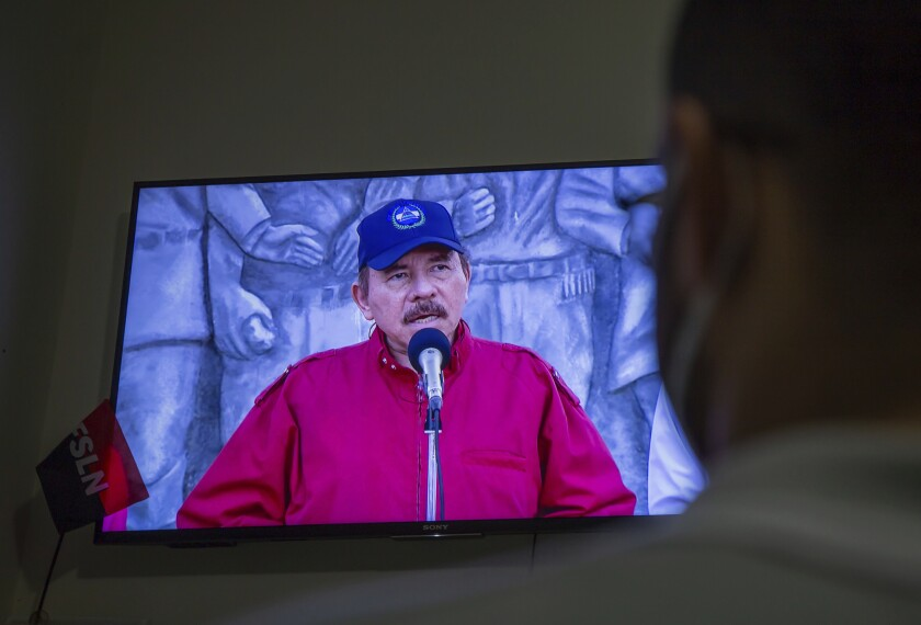 """A man watches a televised national address by Nicaraguan President Daniel Ortega, at his home in Managua, Nicaragua, Wednesday, June 23, 2021. The president of the Inter-American Commission on Human Rights Antonia Urrejola says that Nicaragua has entered a new phase of repression with at least 20 opposition figures arrested in recent weeks and """"constant human rights violations."""" (AP Photo/Miguel Andres)"""