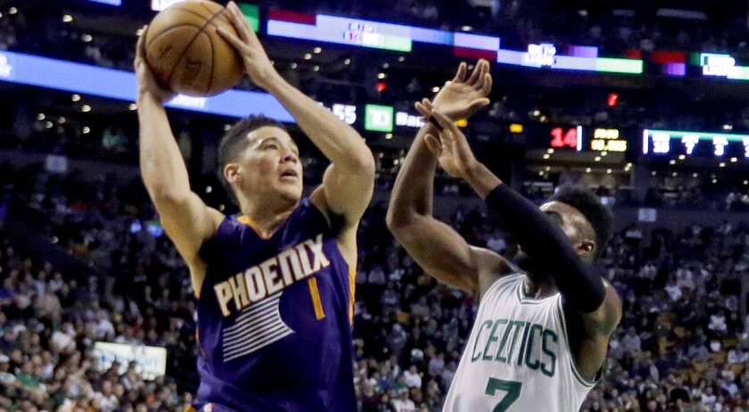 Suns guard Devin Booker drives for a layup against Celtics forward Jaylen Brown during his 70-point game.