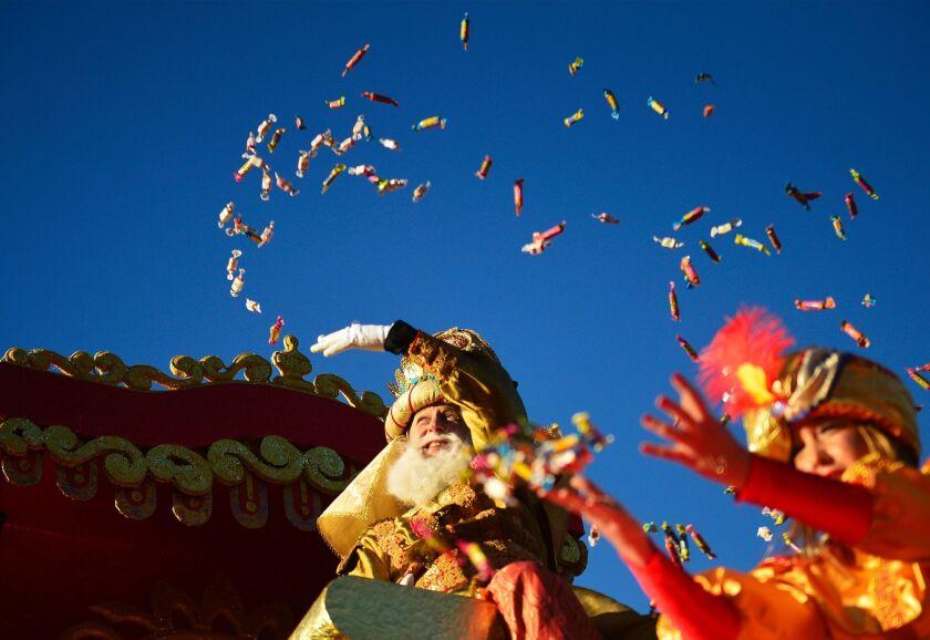 El rey Gaspar, uno de los tres Reyes Magos, y uno de sus pajes, lanza caramelos a los asistentes a la Gabalgata de Reyes que tuvo lugar en Sevilla, España, el pasado jueves 5 de diciembre.