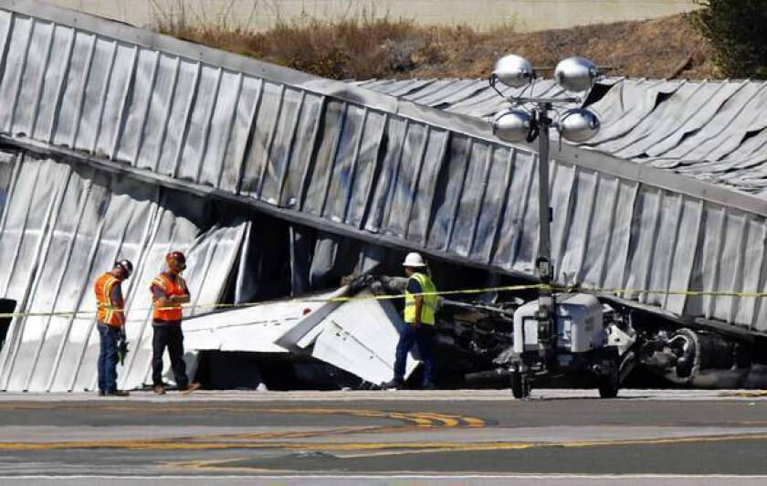 Investigators stand near the tail section of a Cessna jet that crashed at Santa Monica Airport on Sept. 29. City officials have sued the FAA to gain control of the embattled airport, which local groups want to turn into a park.