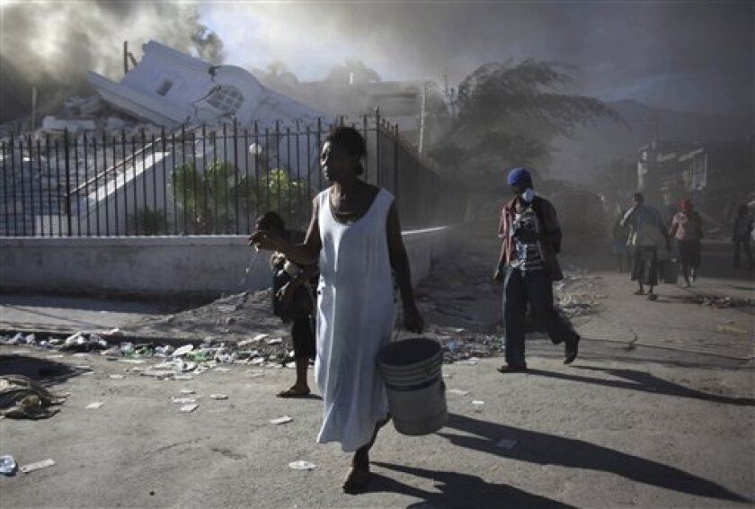 "**  CORRECTS NAME OF COLLAPSED BUILDING TO NATIONAL JUSTICE PALACE  ""  People walks in front of the collapsed National Justice Palace in Port-au-Prince, Saturday, Jan. 16, 2010. Relief groups and officials are focused on moving aid flowing into Haiti to survivors of the powerful earthquake that hit"