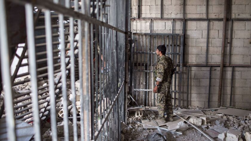 A member of the U.S.-backed Syrian Democratic Forces walks inside a prison in Raqqa, Syria. An American citizen who allegedly fought for Islamic State in Syria has been detained in Iraq for more than two months.