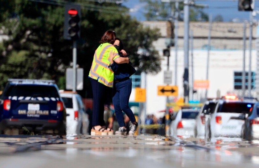 Two people hug outside the scene of a shooting in San Jose, Calif., on Wednesday, May, 26. 2021.