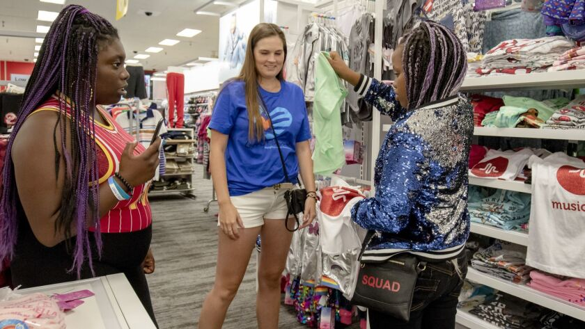 Kristin Hill (center), of the Larry Himmel Foundation, and Destini Jackson, left, assist Daisy Brown with clothes shopping at Target on Saturday. The foundation took the four children of Dorienda Zollicoffer-Jackson, who passed away from uterine cancer, on the shopping trip.
