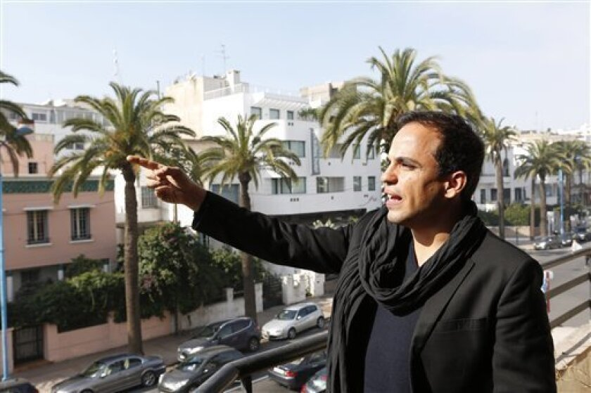 """Kamal Hachkar, director of the documentary """"Tinghir to Jerusalem"""" gestures from a balcony in Casablanca , Friday, Feb, 15, 2013. Once home to some 300,000 Jews, the largest population in the Arab world, Morocco is increasingly taking a fresh look at its long history with Judaism. (AP Photo/Abdeljalil Bounhar)"""