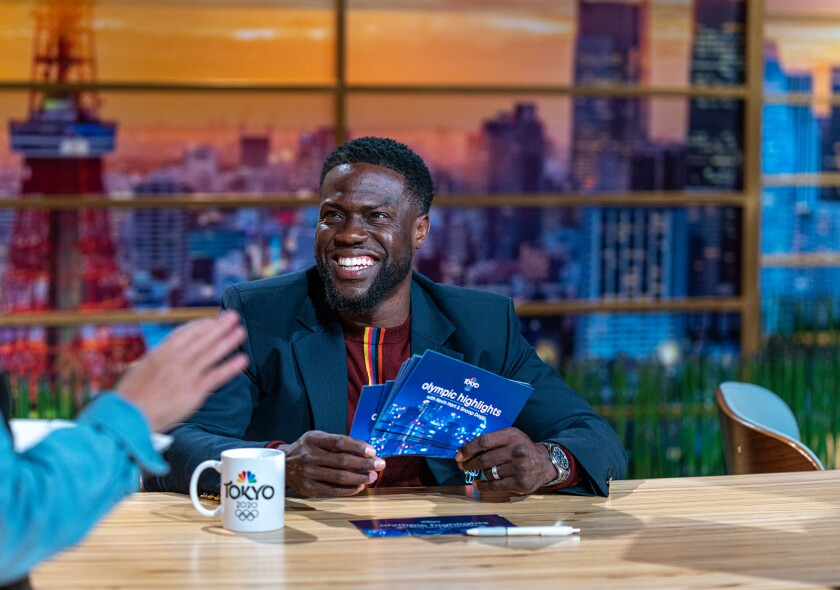 """Kevin Hart tapes smiles while holding notecards that say """"Olympic highlights"""" on the back."""
