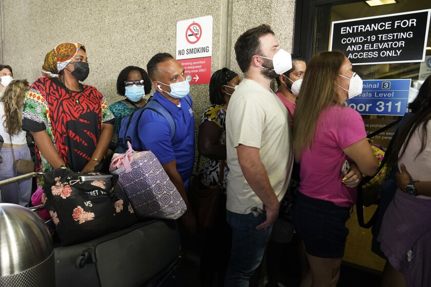 Passengers traveling overseas from Florida wait to get a coronavirus test.