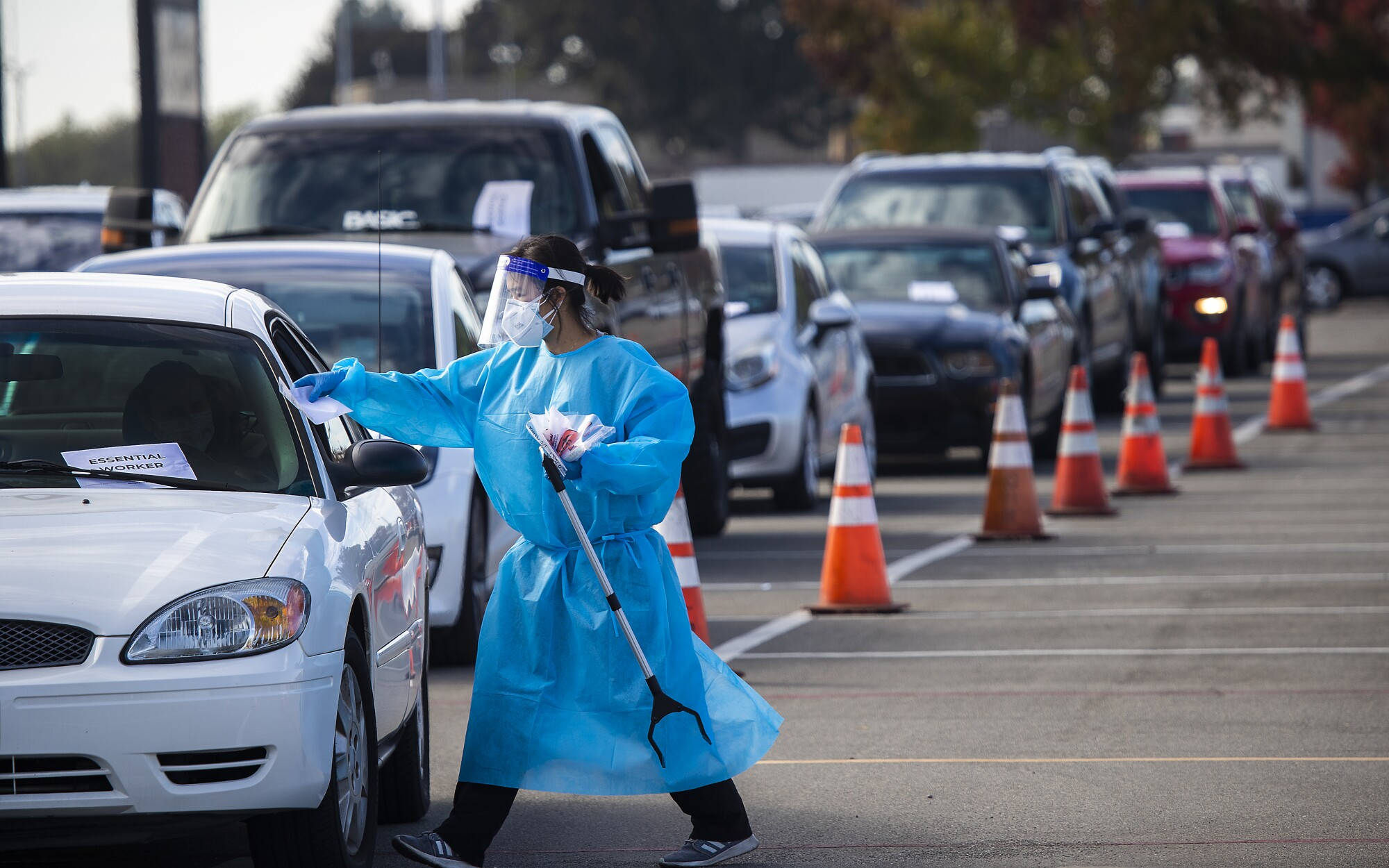 A healthcare worker conducts coronavirus test at a drive-through site in Costa Mesa.