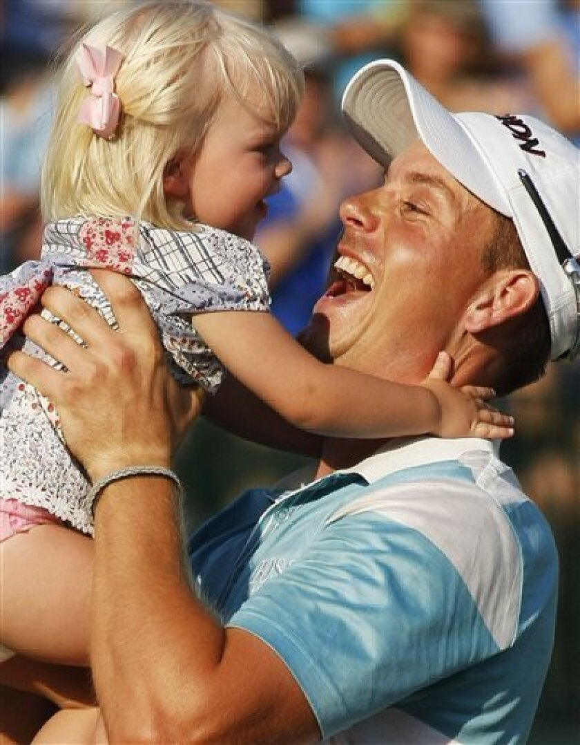 Henrik Stenson, of Sweden, holds up his daughter, Lisa, after his four shot victory at The Players Championship golf tournament at TPC Sawgrass in Ponte Vedra Beach, Fla., Sunday, May 10, 2009. Stenson's 6-under-par round gave him a 12-under-par total. (AP Photo/J Pat Carter)