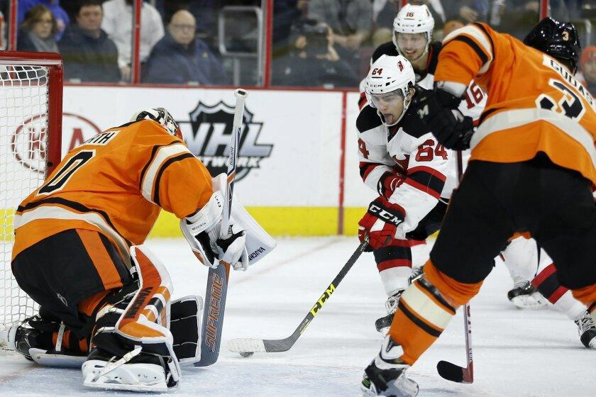 New Jersey Devils' Joseph Blandisi (64) scores a goal against Philadelphia Flyers' Michal Neuvirth, left, and Radko Gudas (3) during the first period of an NHL hockey game, Saturday, Feb. 13, 2016, in Philadelphia. (AP Photo/Matt Slocum)