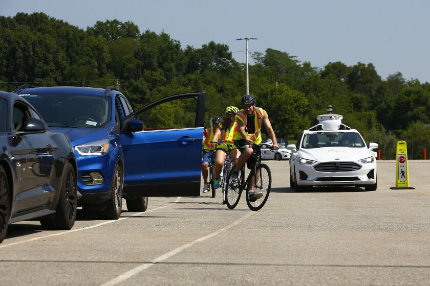 An Argo AI / Ford Motor robot test care avoids bicyclists on a test track.