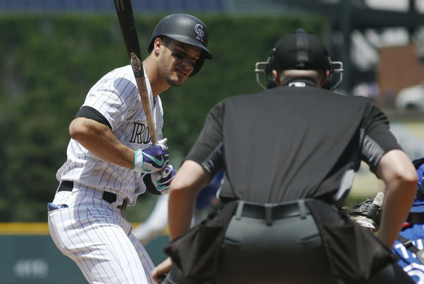 FILE - In this June 29, 2016, file photo, Colorado Rockies' Nolan Arenado, left, reacts as home plate umpire Nic Lentz, right, calls a strike on a pitch from Toronto Blue Jays starting pitcher Aaron Sanchez in the first inning of a baseball game in Denver. (AP Photo/David Zalubowski, File)