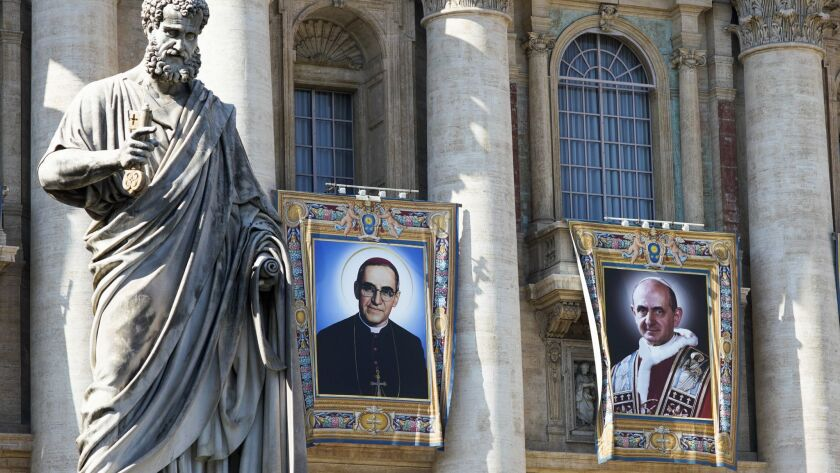 Tapestries depicting Archbishop Oscar Romero, left, and Pope Paul VI hang from a balcony of the facade of St. Peter's Basilica at the Vatican on Saturday.