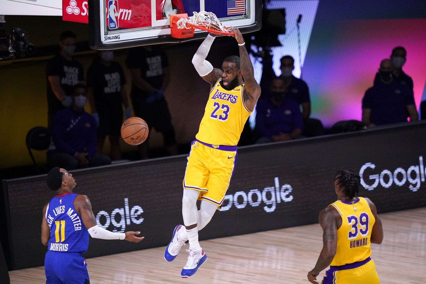 Denver Nuggets guard Monte Morris (11) and Los Angeles Lakers' Dwight Howard (39) look on as LeBron James.
