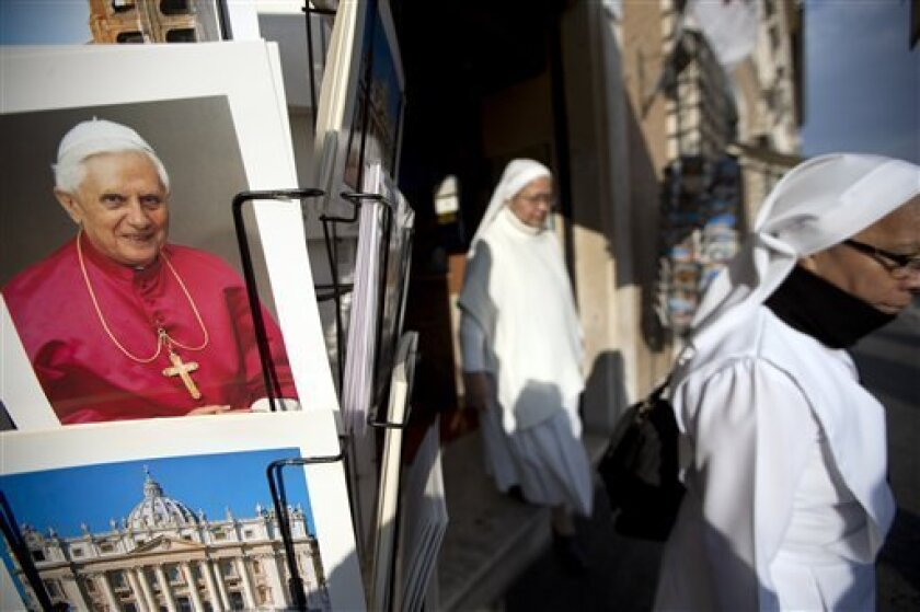 """Two nuns walk past a photo of Pope Benedict XVI as they leave a souvenir shop just outside the Vatican, Tuesday, Feb. 26, 2013. Pope Benedict XVI will be known as """"emeritus pope"""" in his retirement and will continue to wear a white cassock, the Vatican announced Tuesday, again fueling concerns about potential conflicts arising from having both a reigning and a retired pope. The pope's title and what he would wear have been a major source of speculation ever since Benedict stunned the world and announced he would resign on Thursday, the first pontiff to do so in 600 years. (AP Photo/Andrew Medichini)"""