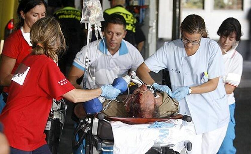 A medical team tends an injured passenger in Madrid's Barajas airport after a Spanair jetliner bound for the Canary Islands swerved off the runway and caught fire.