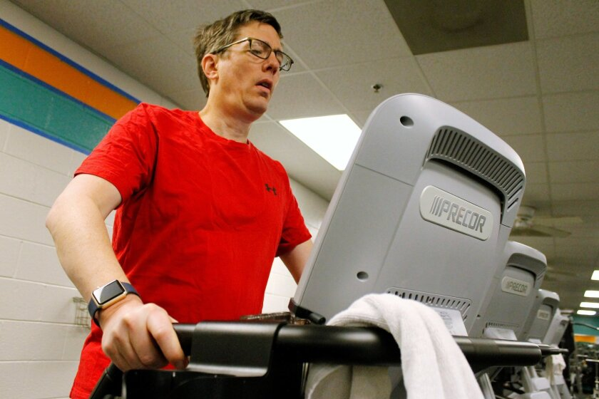 Mark Holloway of Clemmons, N.C., goes through part of his exercise routine at the Jerry Long YMCA in Clemmons, Tuesday, March 1, 2016. Holloway got a $350 Apple Watch for just $25 by meeting exercise goals for two years. The program was offered through three U.S. companies. (AP Photo/Skip Foreman)